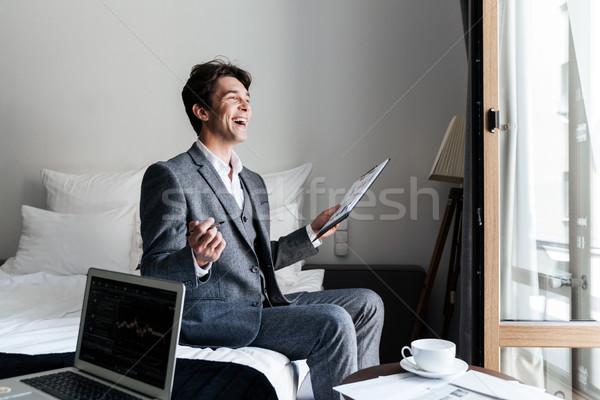 Jonge lachend mannelijke advocaat documenten hotelkamer Stockfoto © deandrobot