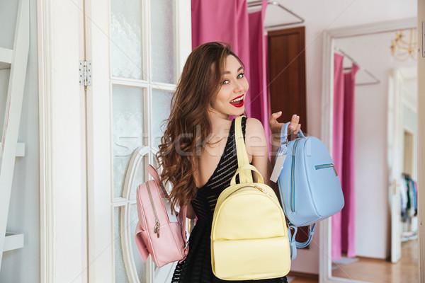 Happy woman indoors holding three backpacks Stock photo © deandrobot