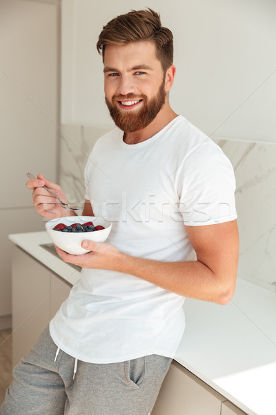 Vertical image of smiling bearded man eating fruit Stock photo © deandrobot