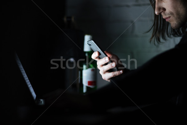 Concentrated man using laptop computer and mobile phone Stock photo © deandrobot