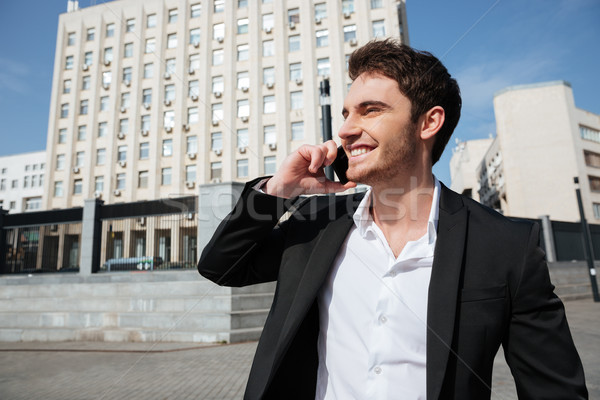 Stock photo: Smiling young businessman walking outdoors.