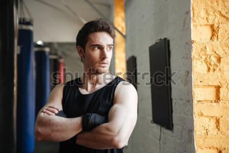 Vertical shot of boxer near punching bag Stock photo © deandrobot
