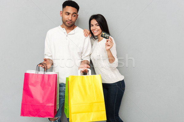 Stock photo: Loving couple standing over grey wall and holding shopping bags