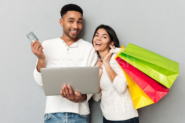 Woman with packages and man with credit card looking camera Stock photo © deandrobot