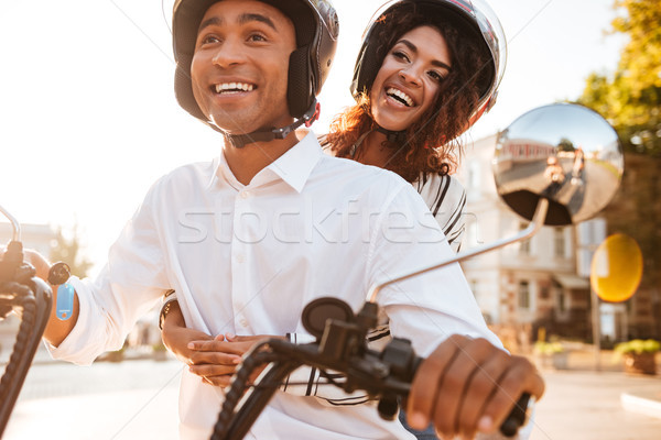 Image of Happy african couple rides on modern motorbike Stock photo © deandrobot