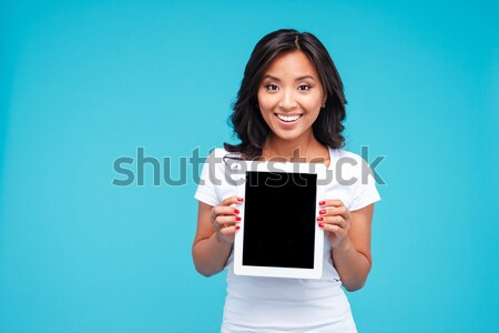 Portrait of a happy smiling woman showing blank screen tablet Stock photo © deandrobot