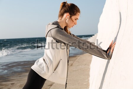 Photo of young slim sport woman doing push-ups while standing ne Stock photo © deandrobot
