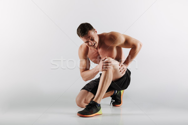 Displeased young sportsman have painful feelings in leg. Stock photo © deandrobot