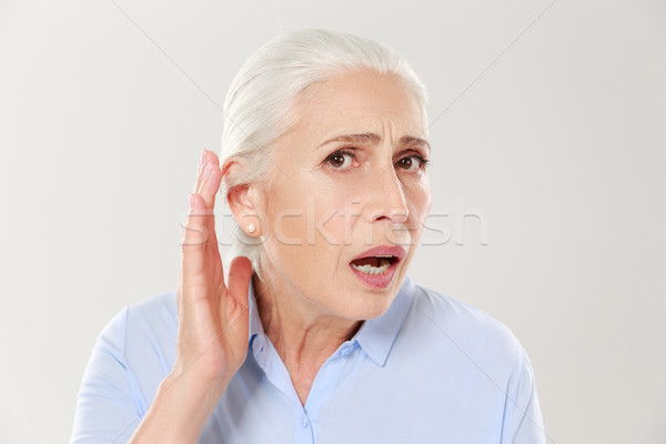 Close-up  of charming elderly woman, holding hand by her ear and Stock photo © deandrobot