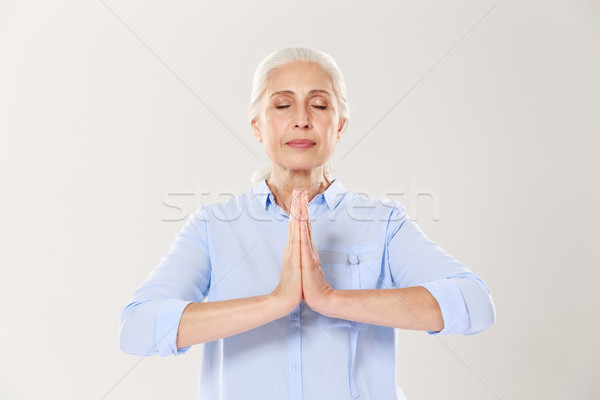 Senior woman practising yoga holding hands in namaste and keepin Stock photo © deandrobot