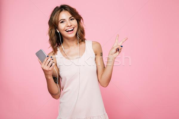 肖像 笑みを浮かべて 魅力的な女の子 音楽を聴く イヤホン 立って ストックフォト © deandrobot