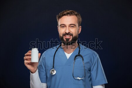 Careful doctor holding glass of water isolated Stock photo © deandrobot
