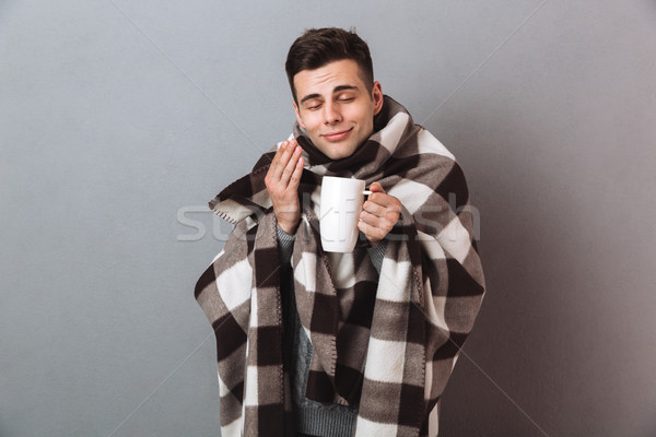 Pleased man in warm plaid holding hot tea smells it. Stock photo © deandrobot