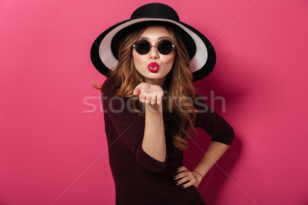 Amazing lady wearing hat and sunglasses blowing kisses. Stock photo © deandrobot