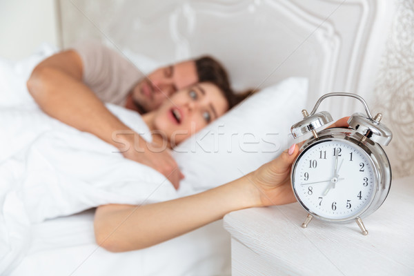 Side view of Surprised couple sleeping together in bed Stock photo © deandrobot