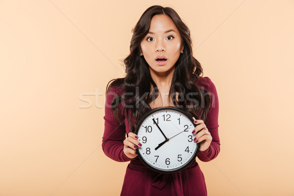 Young asian woman with curly long hair holding clock showing nea Stock photo © deandrobot
