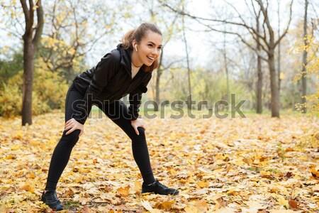 Portré komoly fitnessz lány fülhallgató nyújtás Stock fotó © deandrobot