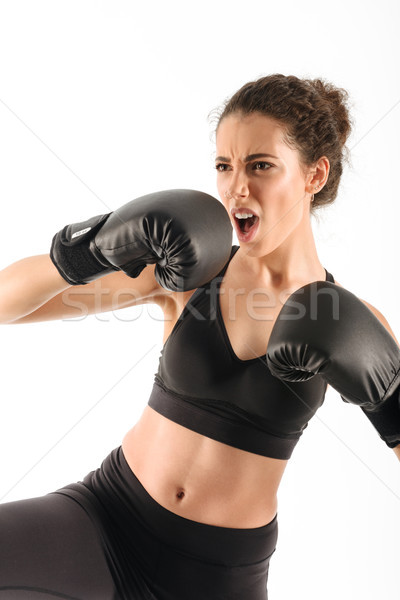 Vertical image of cool screaming curly brunette fitness woman Stock photo © deandrobot