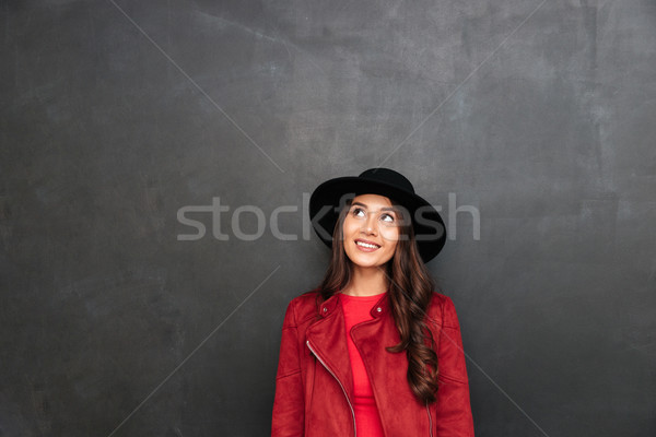 Happy young woman wearing hat looking aside. Stock photo © deandrobot