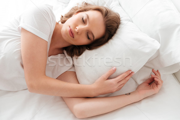 Sleeping young woman lies in bed with eyes closed. Stock photo © deandrobot
