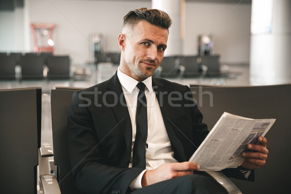 Smiling businessman reading newspaper Stock photo © deandrobot