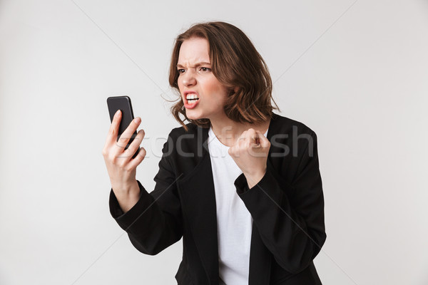 Agressive young woman standing isolated talking by phone Stock photo © deandrobot