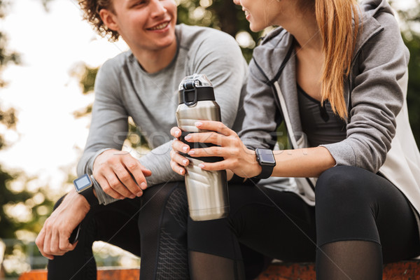 Image of young sporty couple man and woman 20s in tracksuits, ta Stock photo © deandrobot