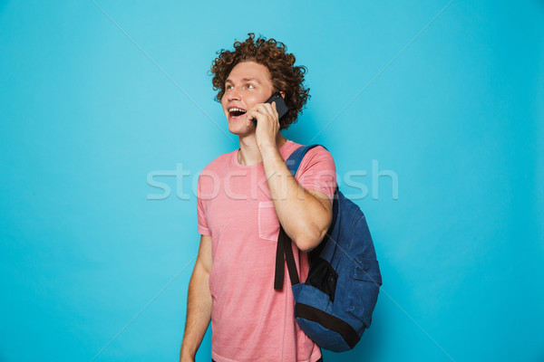 Photo of college guy with curly hair wearing casual clothing and Stock photo © deandrobot