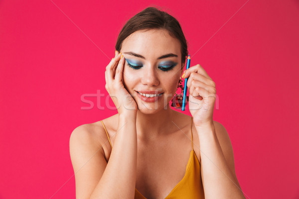 Image of lovely posh woman 20s wearing earrings smiling and appl Stock photo © deandrobot