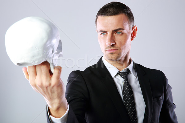 Businessman holding skull and looking on it over gray background Stock photo © deandrobot