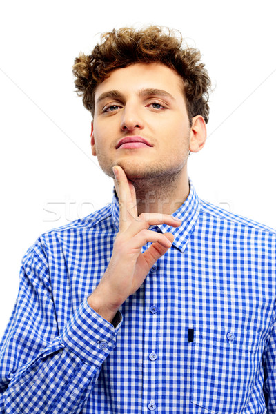 Young casual man touching his chin over white background Stock photo © deandrobot