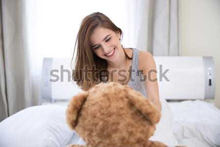 Piękna młoda kobieta posiedzenia bed miś baby Zdjęcia stock © deandrobot