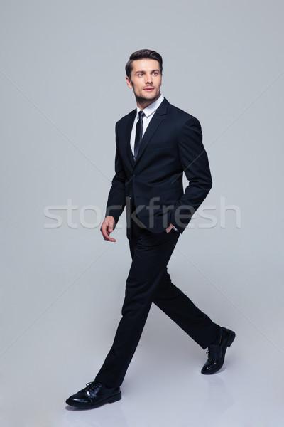 Businessman walking over gray background Stock photo © deandrobot