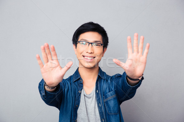 Happy asian man in glasses making stop gesture Stock photo © deandrobot