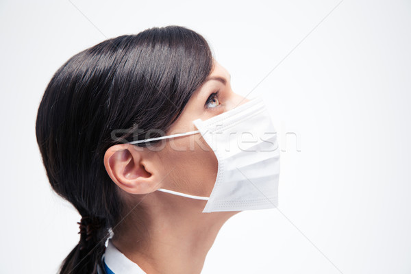 Female medical doctor in mask looking up  Stock photo © deandrobot