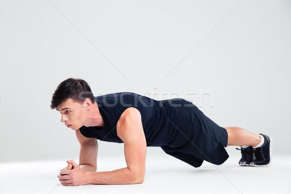 Sports man doing elbow plank exercises  Stock photo © deandrobot