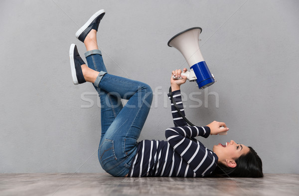 Young woman lying and speaking in megaphone Stock photo © deandrobot