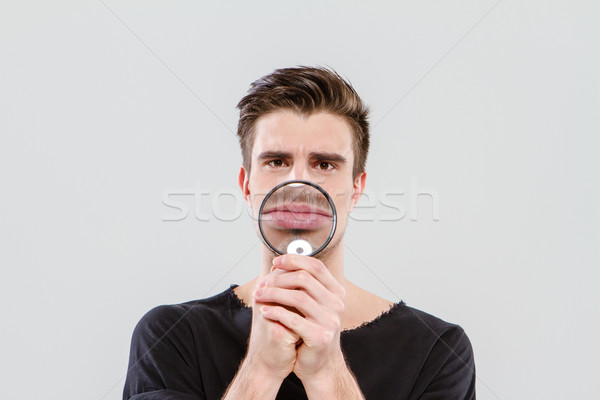 Funny man playing tricks using magnifying glass Stock photo © deandrobot