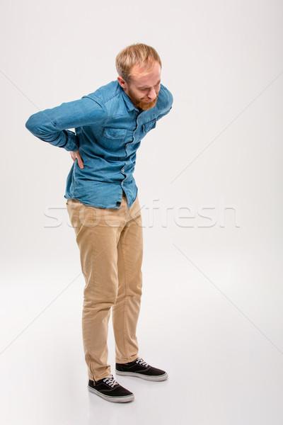 Full length portrait of young bearded man having back pain Stock photo © deandrobot