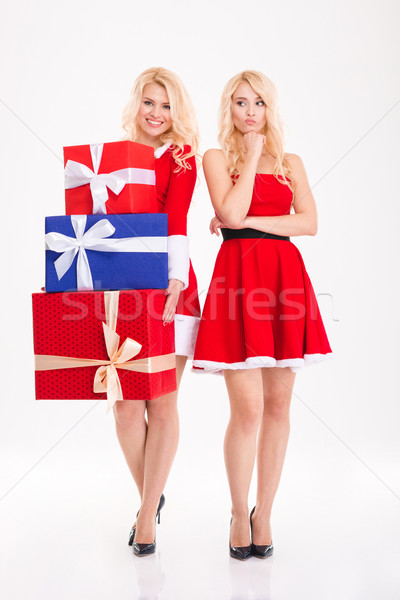 Joyful and unhappy blonde sisters twins sharing gifts  Stock photo © deandrobot