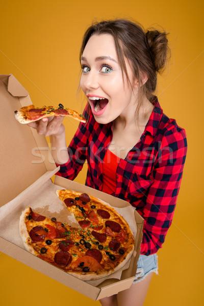 Alegre encantador mulher jovem em pé degustação pizza Foto stock © deandrobot
