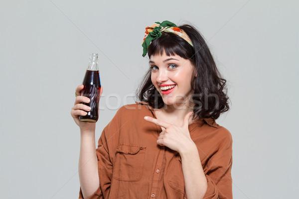 Mosolyog gyönyörű nő mutat üveg édes szénsavas Stock fotó © deandrobot