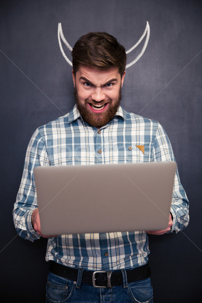 Funny man using laptop over blackboard background with drawn horns Stock photo © deandrobot