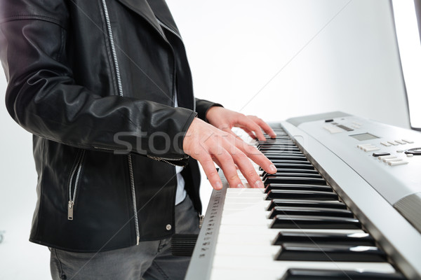 Hands of young man standing and playing on synthesizer Stock photo © deandrobot
