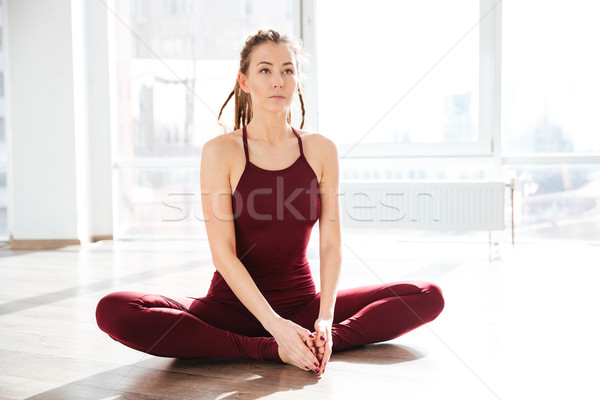 Concentrated woman stretching and doing yoga in studio Stock photo © deandrobot