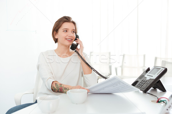 Smiling woman sitting in office and talking on telephone Stock photo © deandrobot