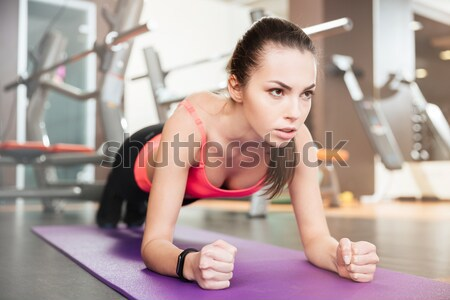 Concentrated beautiful young sportswoman doing plank exercise Stock photo © deandrobot