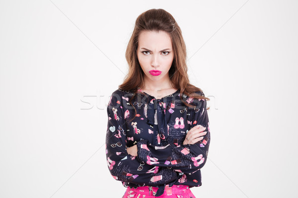 Stock photo: Angry offended young woman standing with arms crossed