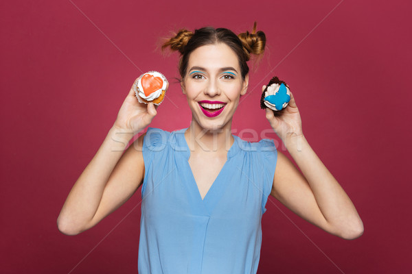 Stock photo: Funny happy young woman standing and holding cupcakes