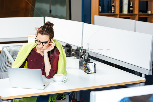 Businesswoman working with laptop and feeling cold in office Stock photo © deandrobot